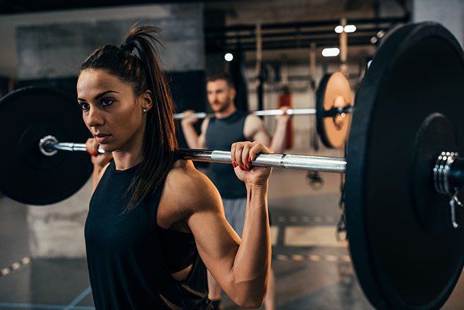 Young woman working out using a barbell at the gym
