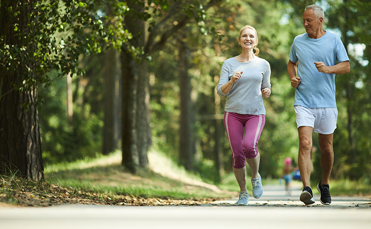 Active and healthy aged couple running in natural environment on summer morning